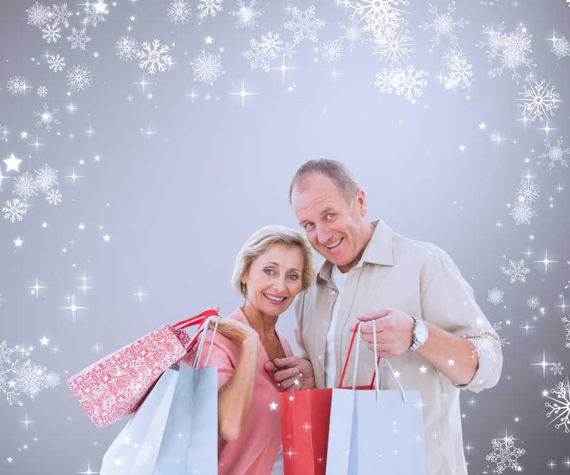 雪花背景的夫妇手拿购物袋