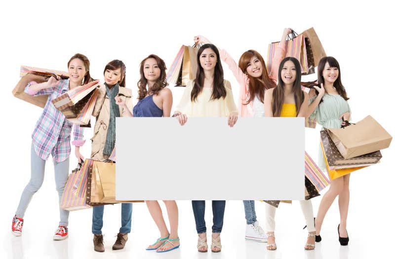 迷人的亚洲妇女购物和空白广告牌