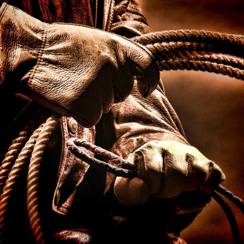 牛仔带着皮手套拿着套绳