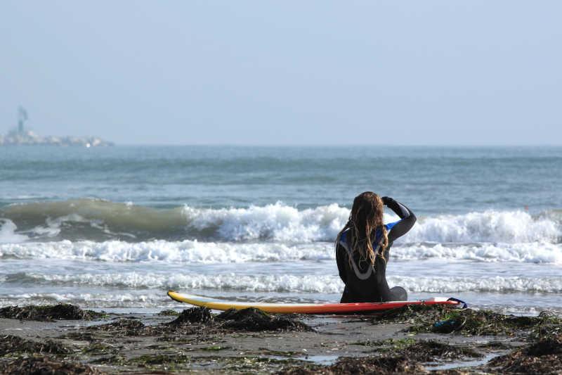 坐在海岸边准备冲浪的美女