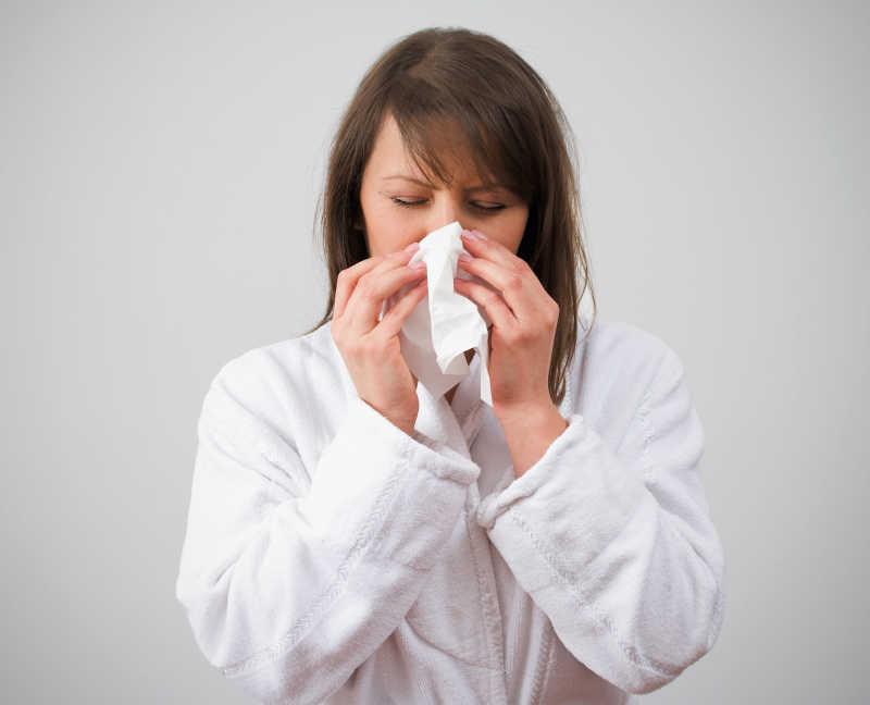正在擦鼻子感冒的女人