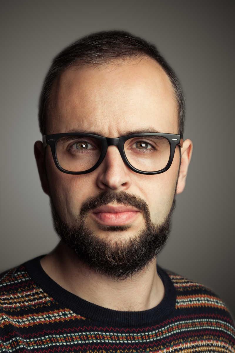 灰色背景下戴着眼镜留着胡子的男人