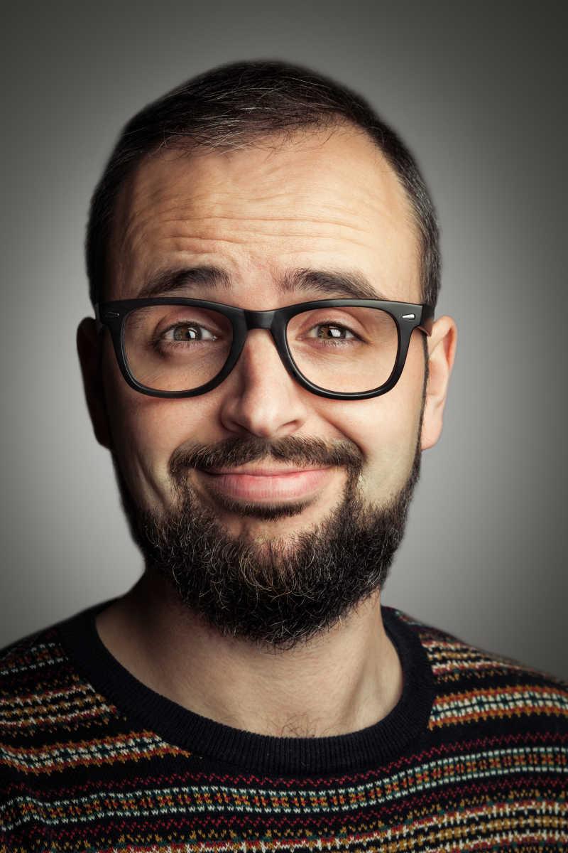 灰色背景下戴着眼镜有络腮胡的微笑的男人