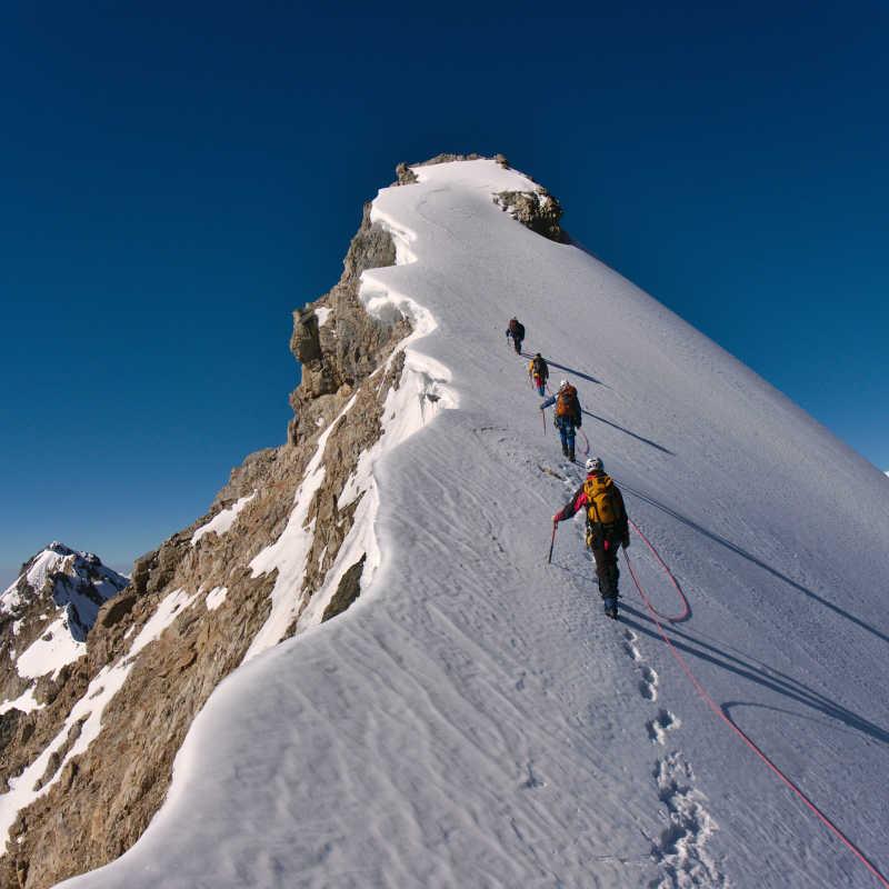 沿着一根绳子即将攀登顶峰的登山者