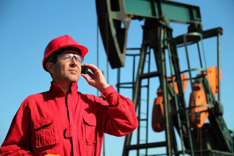 正在打电话的石油工人