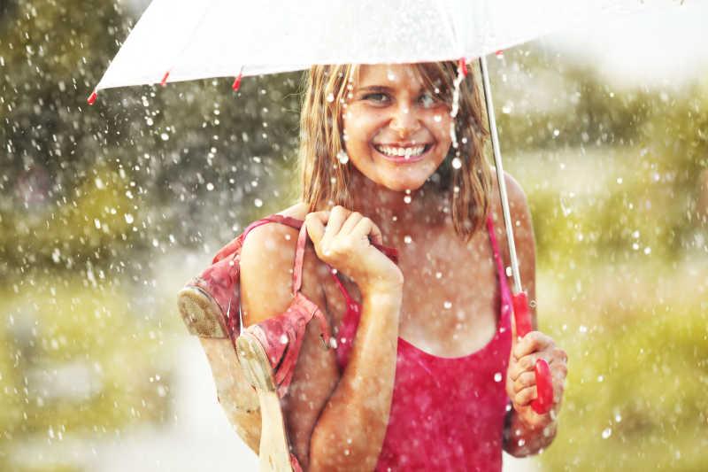 雨中撑着伞的女人手上提着一双鞋