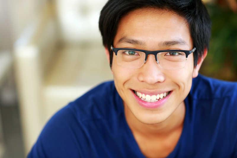 室内背景下穿蓝色衣服微笑的亚裔男子