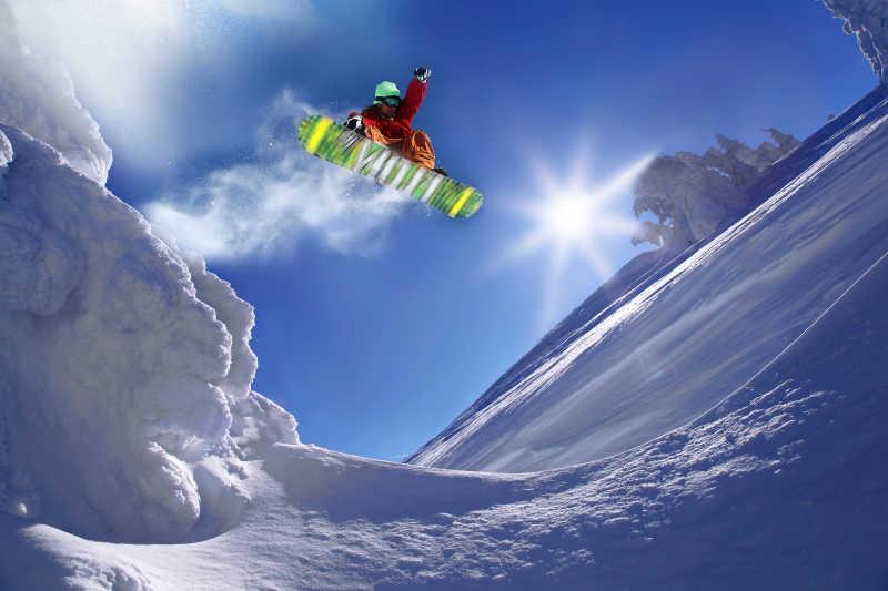 晴天阳光下跳跃而起的单板滑雪运动员
