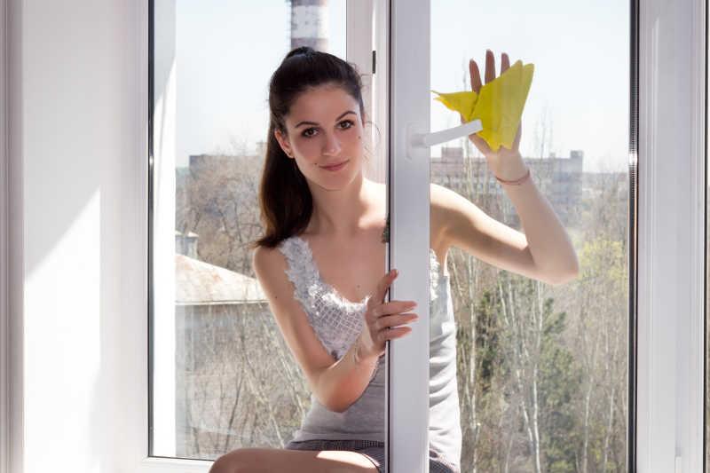 年轻的女孩仔细地清洗窗户