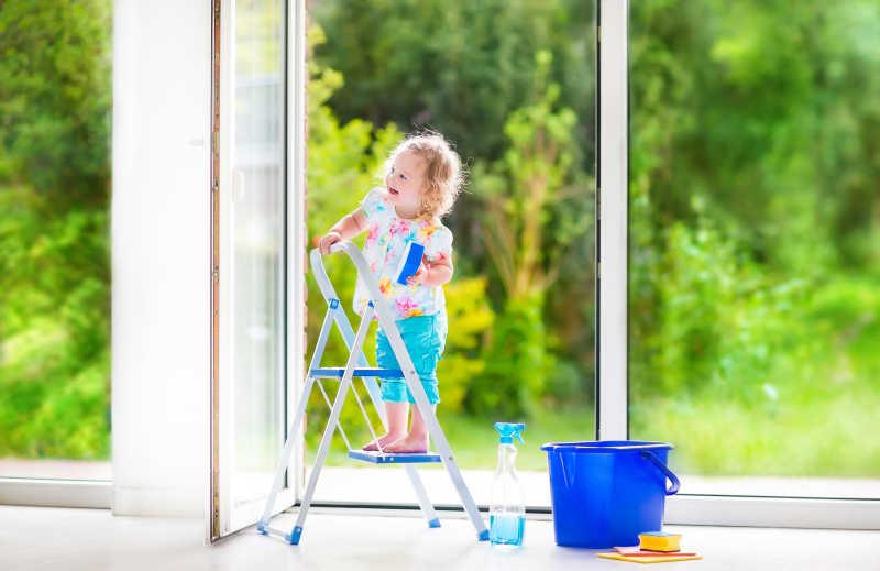 可爱的女孩在花园里洗窗户