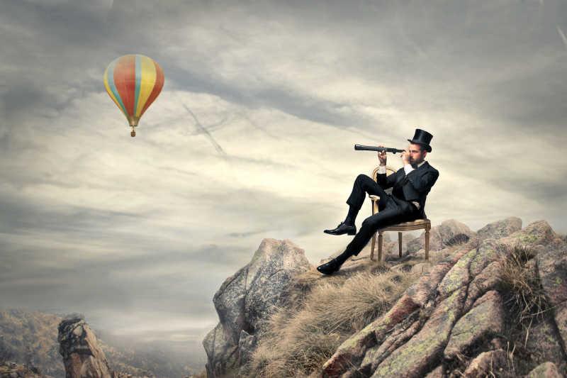 多云有热气球的天空背景下商人坐在山顶拿着望远镜观看风景