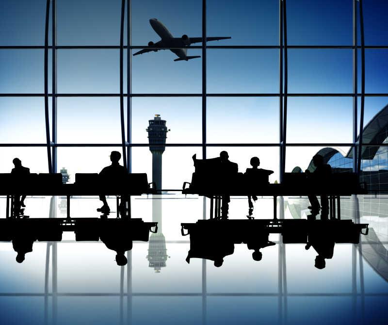 坐在候机室椅子上等飞机的人们剪影