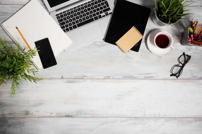 木桌上的笔记本电脑和旁边的办公用品