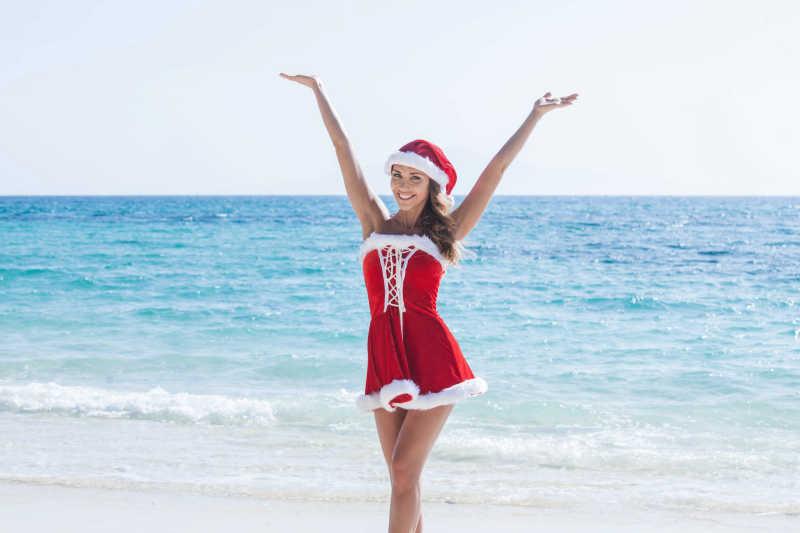 在海滩上举着双手的微笑的美女