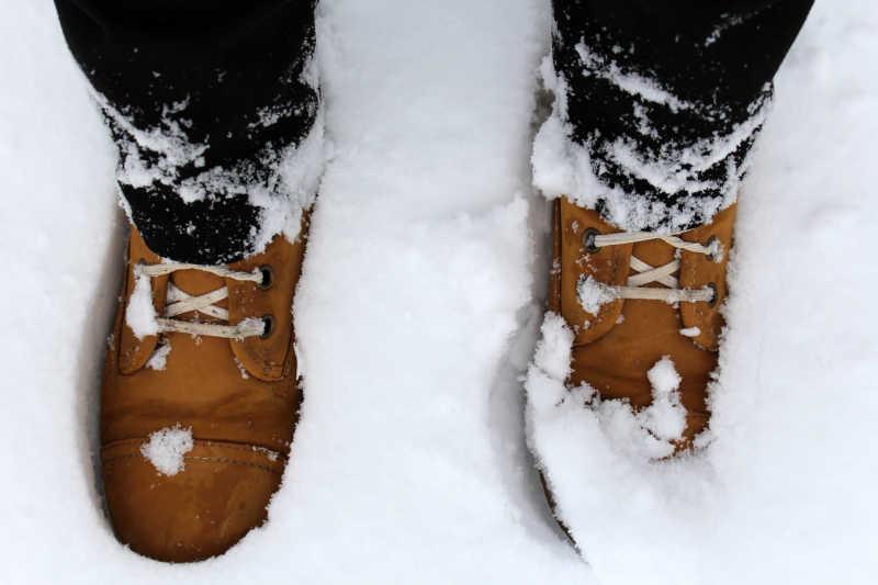 雪地里穿着棕色靴子的腿