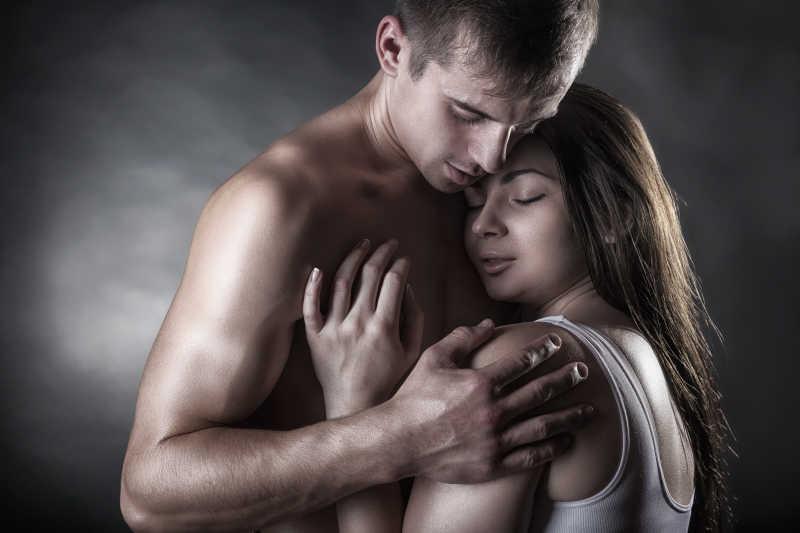黑暗的背景下年轻漂亮的夫妇互相拥抱