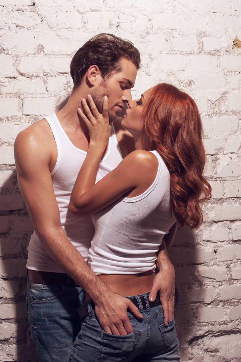 在墙角下男人抚摸着女孩屁股接吻