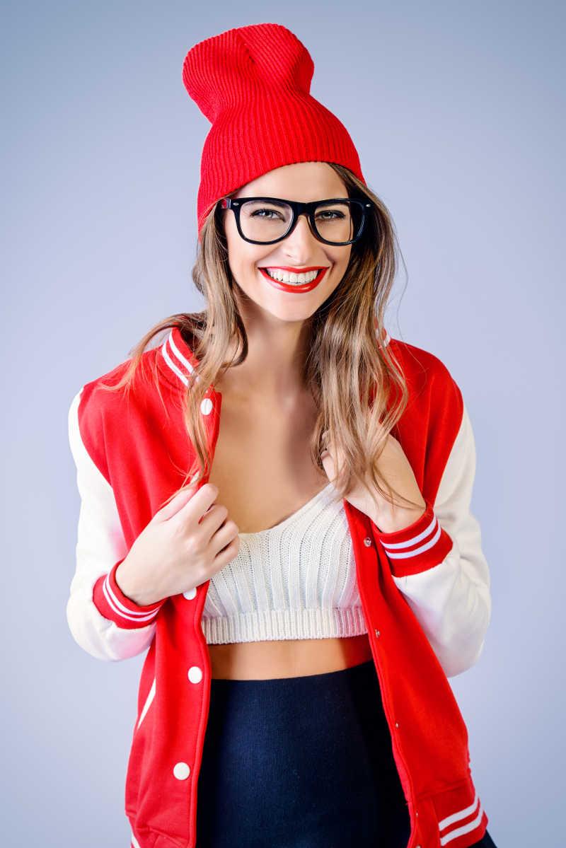 一个穿着鲜红色嘴唇的女孩穿着现代针织帽和运动夹克