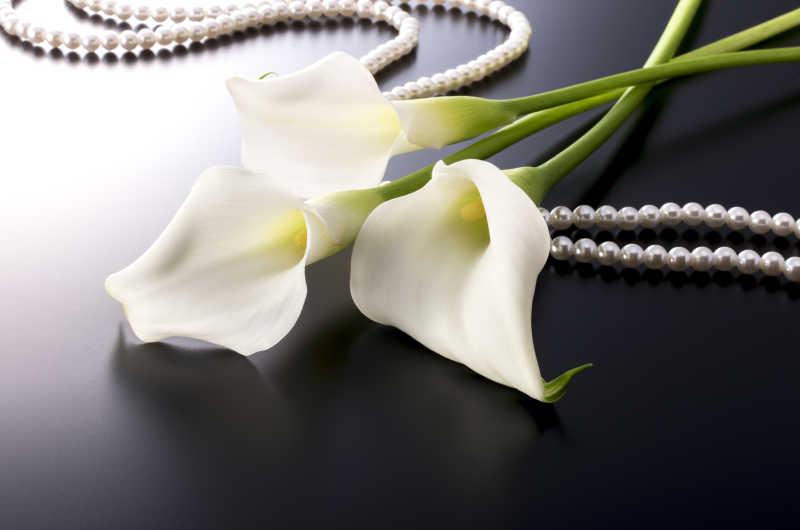黑色背景中的白合花和珍珠链