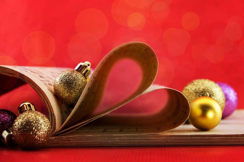 在红色背景下的心形书页和金色的小球