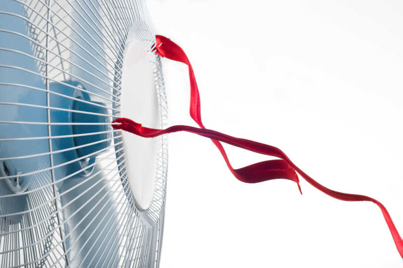 白色背景下绑着红色丝带的风扇