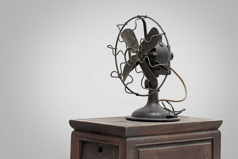 灰色背景下放在木桌上的电风扇