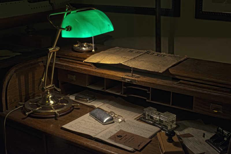 摆放着旧报纸和老式的旧台灯的复古的办公桌