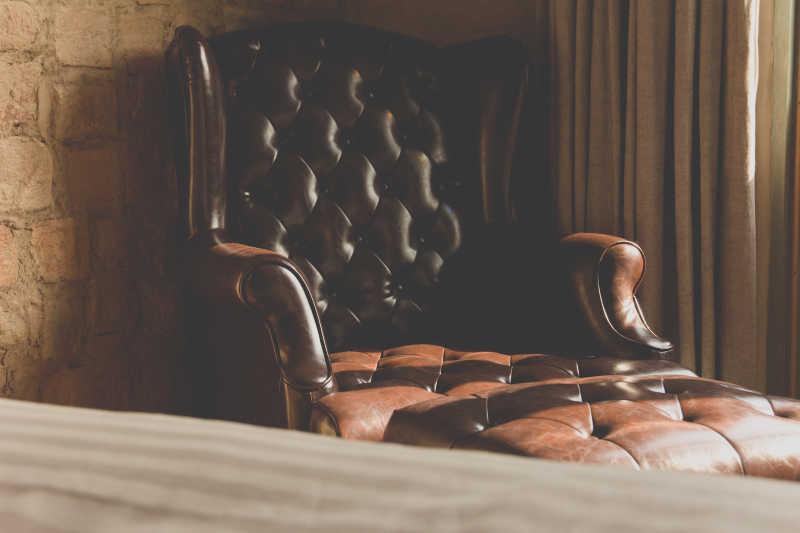 放在墙角的老式的带有扶手的皮椅