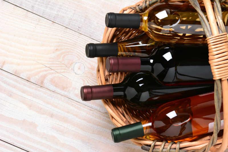 木质桌板上的篮子里的满满的酒瓶