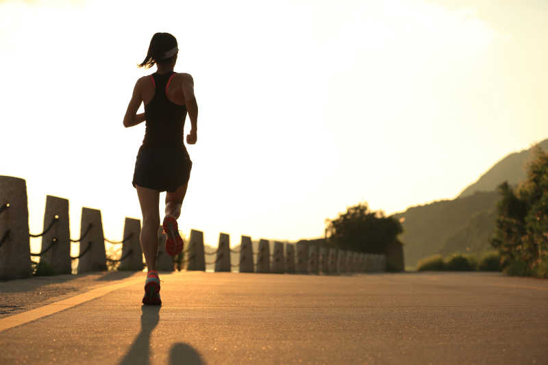 年轻健身女在日出海边跑步