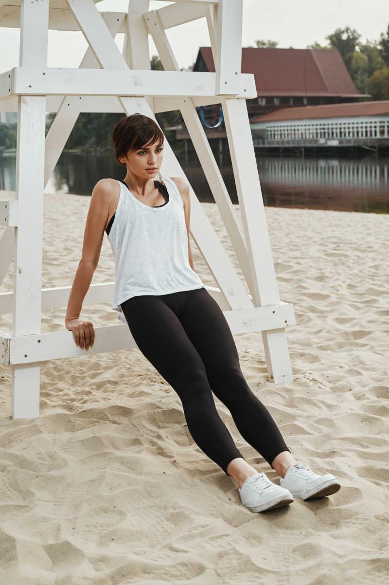 在沙滩上健身的可爱黑发美女