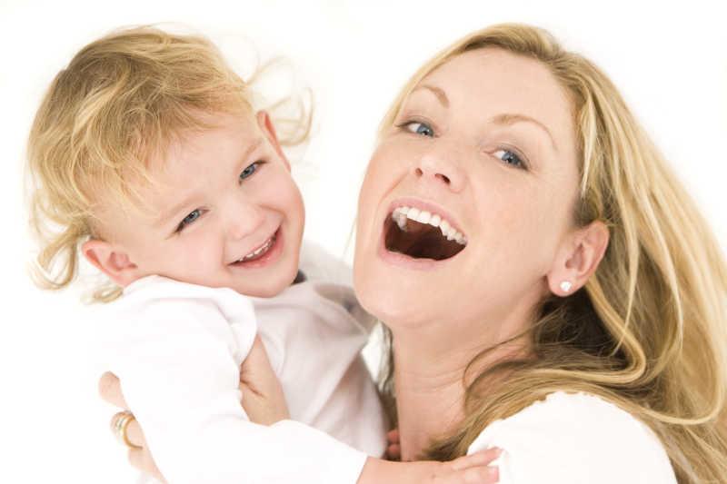 白色背景下大笑的母子