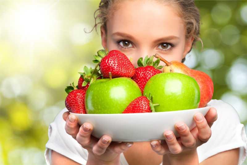 年轻女人端着一盘新鲜水果