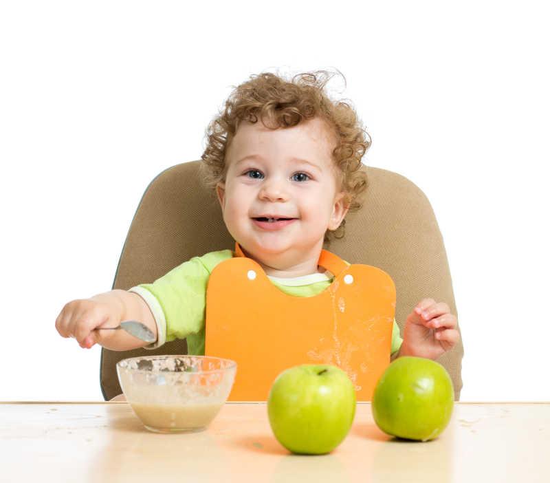 小孩坐在桌子旁用勺子吃饭