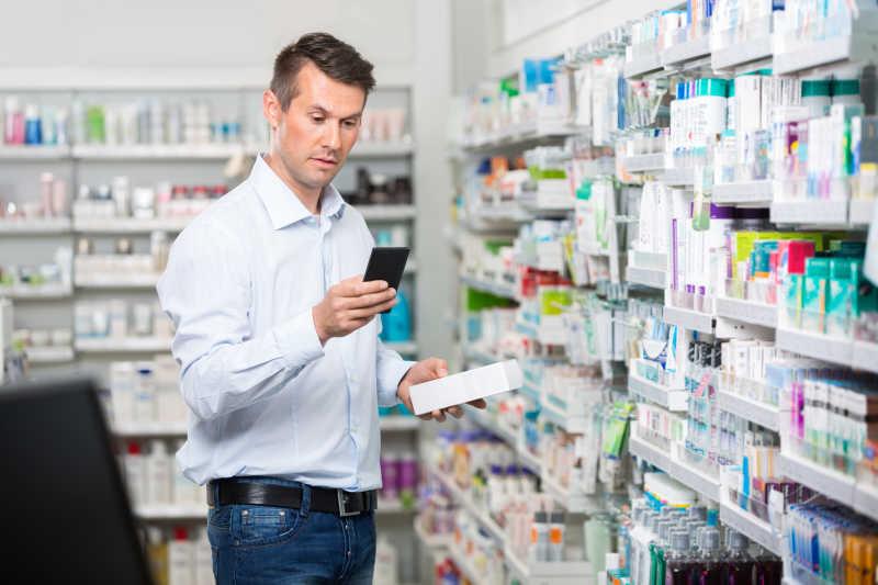 在药店里用手机查询信息的成熟男性