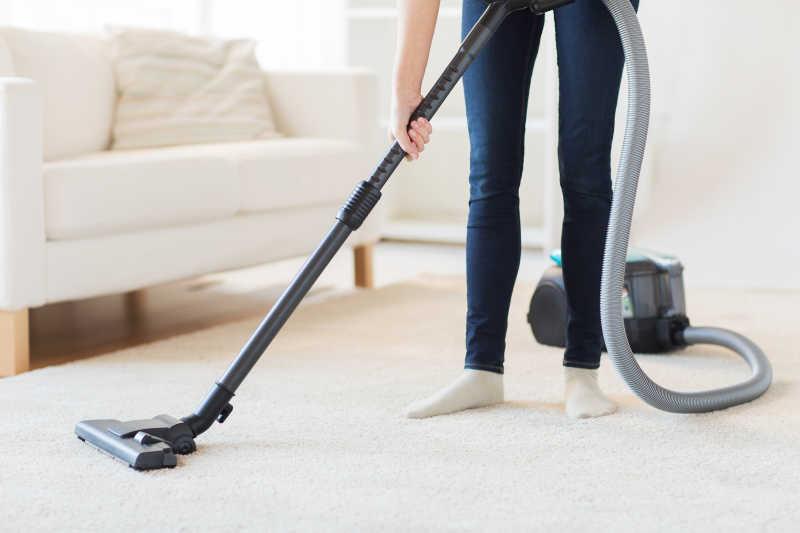 用吸尘器清扫家庭地毯的年轻女孩
