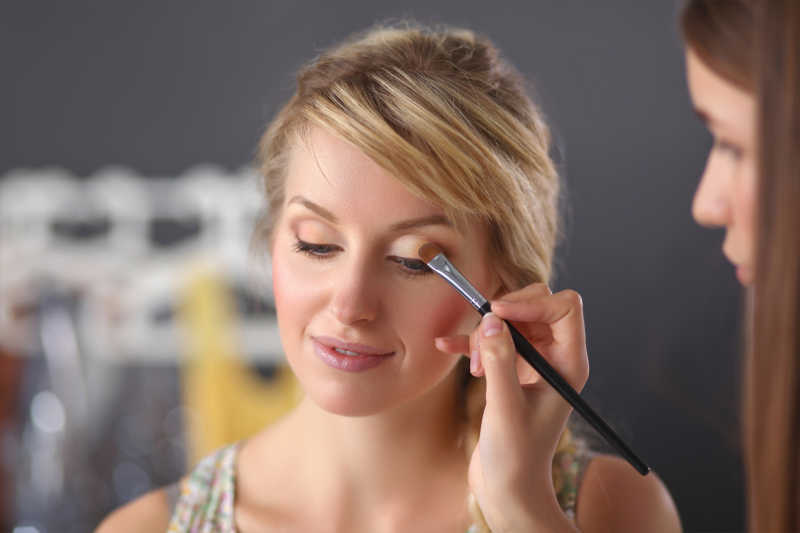 化妆艺术家运用白色眼影在化妆