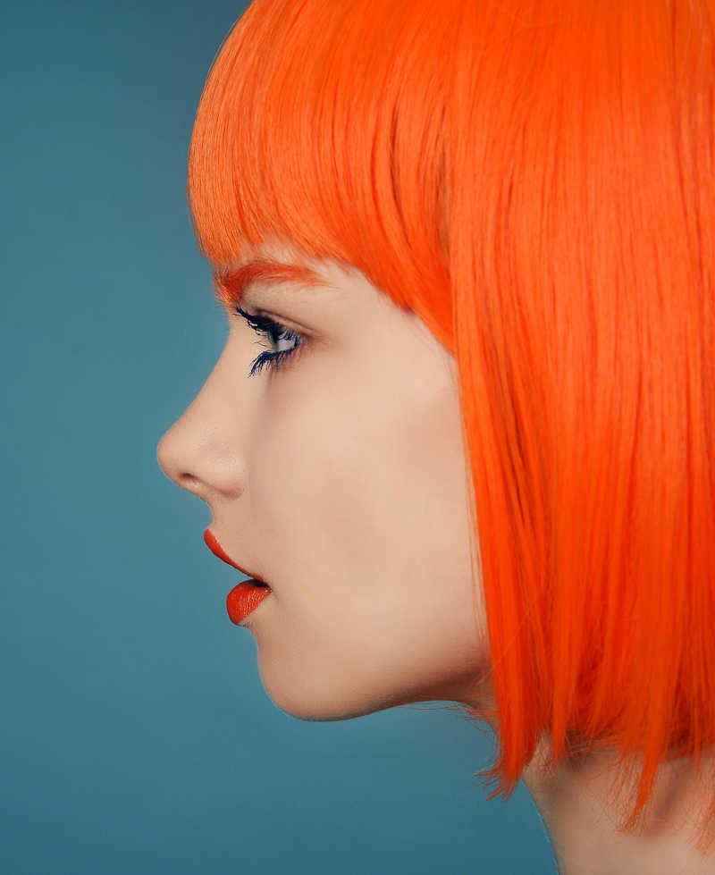 蓝色背景下红发时尚女郎