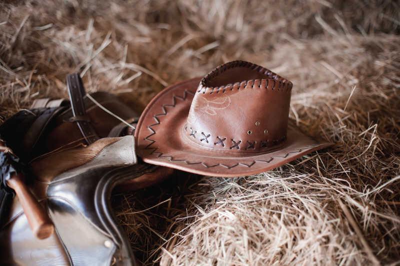 放在草堆上的牛仔帽子与牛仔装备