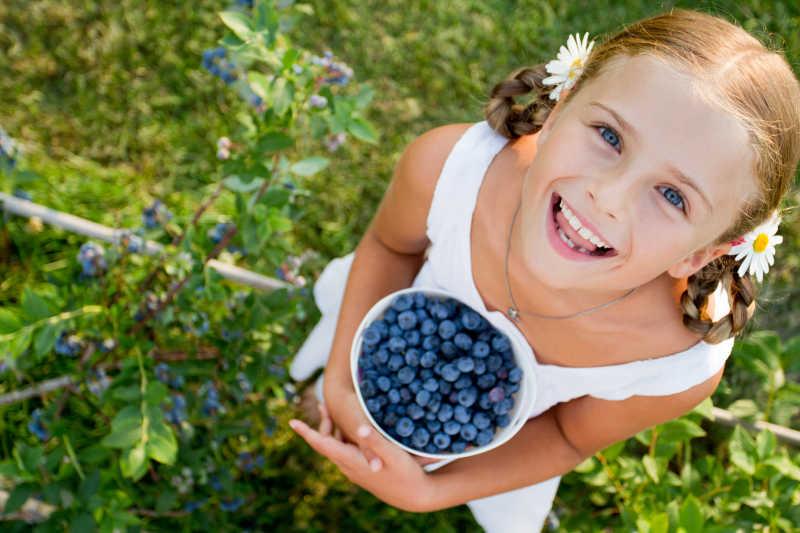 捧着一杯蓝莓的女孩子