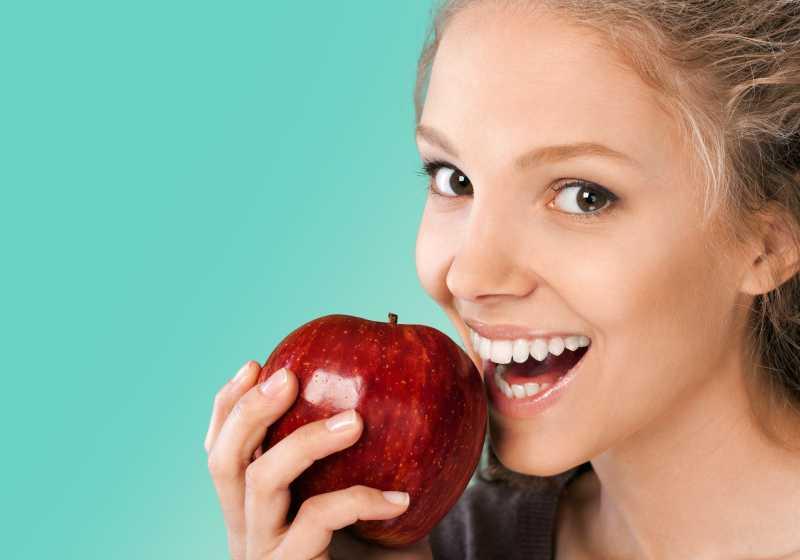 拿着红苹果咬的女人