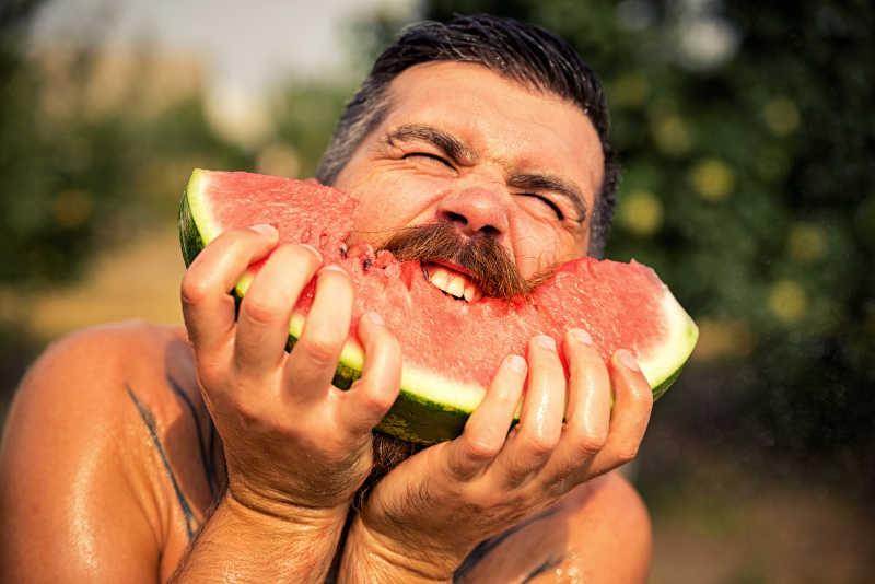 长着胡子的中年男性在吃西瓜