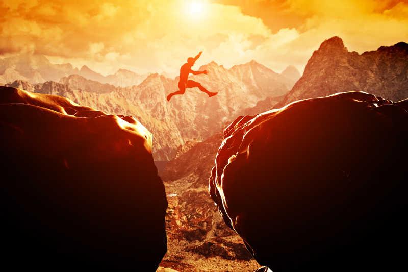 日落时在两座山峰之间跳过悬崖的人