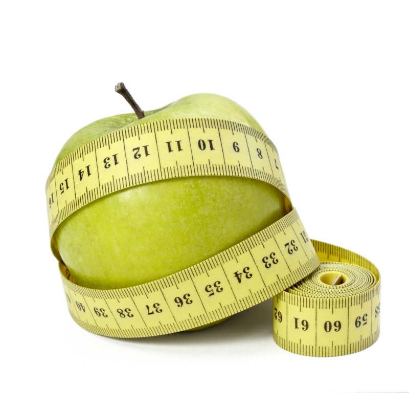 在白色背景下青苹果上缠绕的卷尺