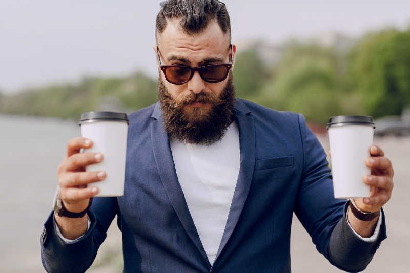 端着咖啡的成熟大胡子男人