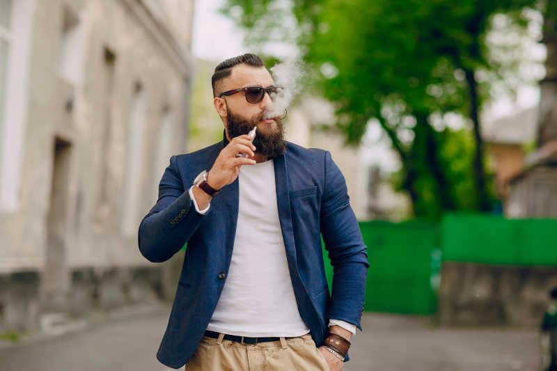 街头的成熟胡子男士与烟