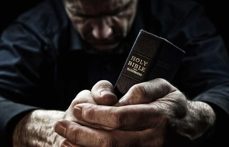 手持圣经正在祈祷的人