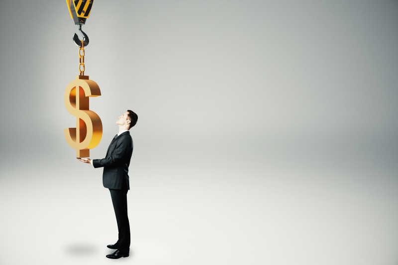 商人将美元样式的挂件挂在吊机挂勾上