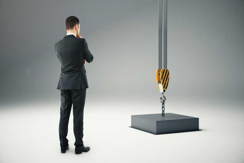 站在吊机吊着的黑块旁边思考的商人
