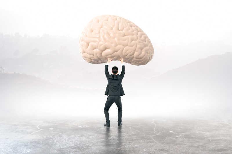 双手举起一个大脑的中年商人